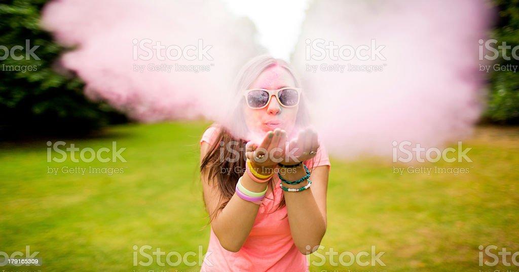 Hipster teenager blowing colorful Holi Powder at camera stock photo
