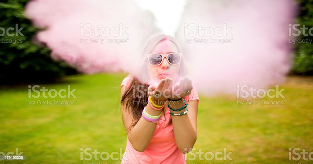 Hipster teenager blowing colorful Holi Powder at camera stock photo