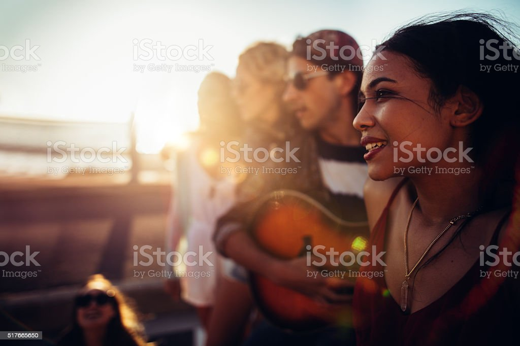 Hipster teenager friends relaxing at beach with a guitar stock photo