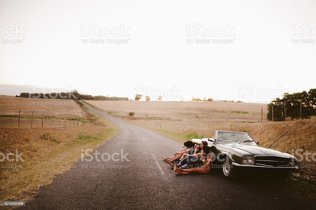 Hipster teenager friends relaxing near to a vintage convertible outside stock photo