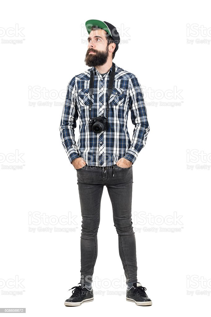 Hipster wearing black dslr camera over neck looking away stock photo
