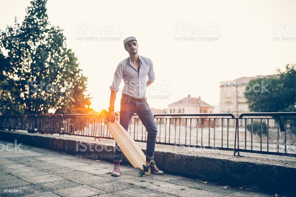 Hipster with a longboard stock photo