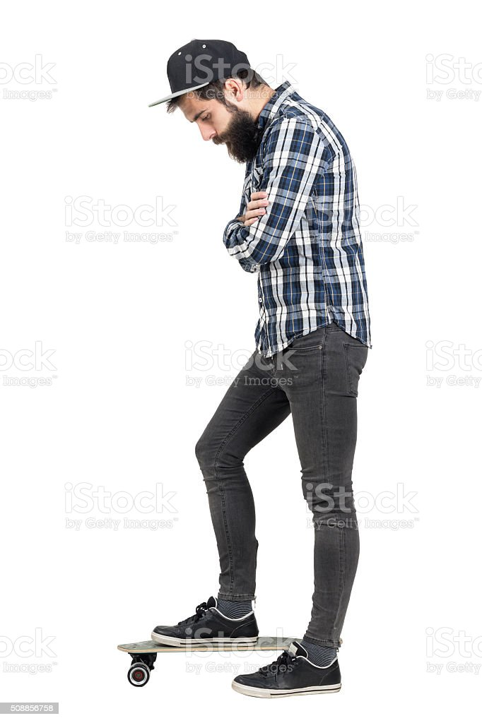 Hipster with crossed arms looking down standing on skate board stock photo