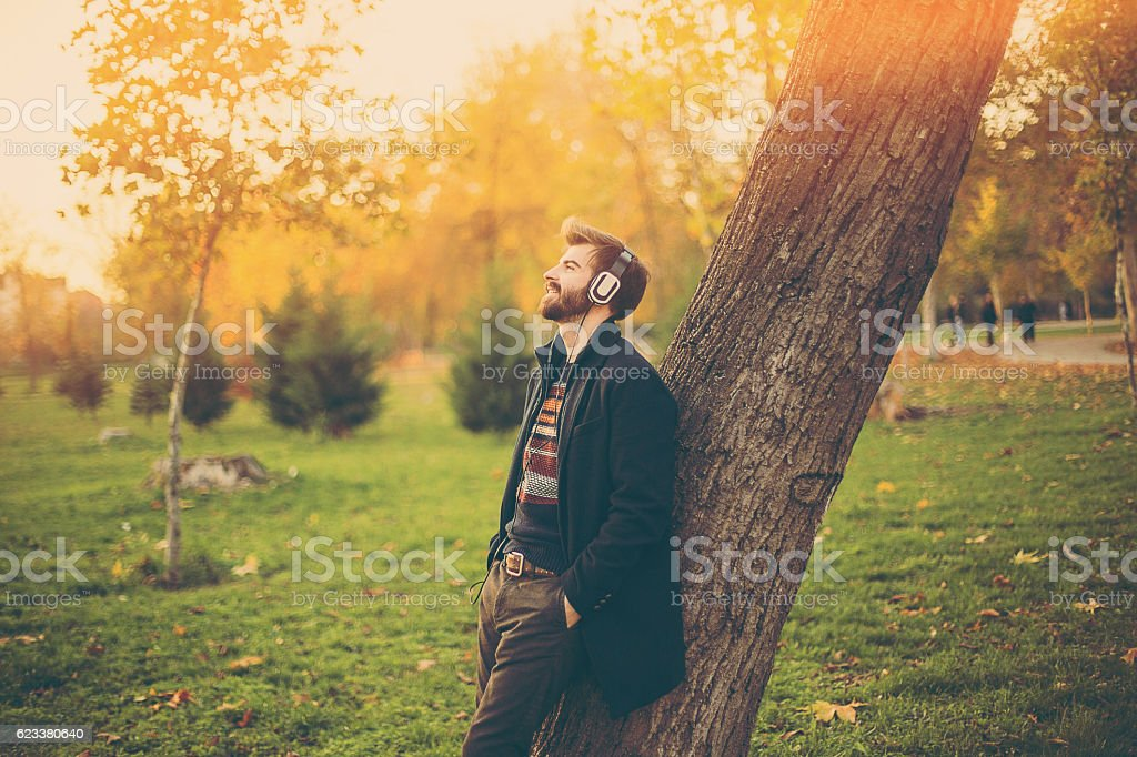 Hipster with headphones leaning on the tree in park stock photo