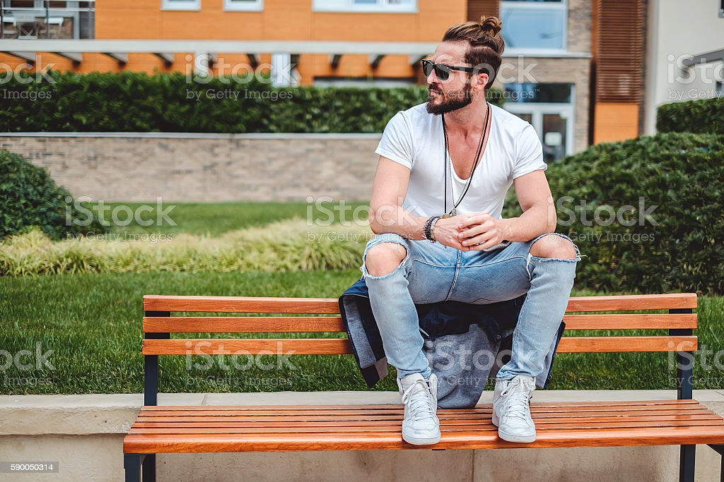 Hipster with man bun sitting on the park bench stock photo