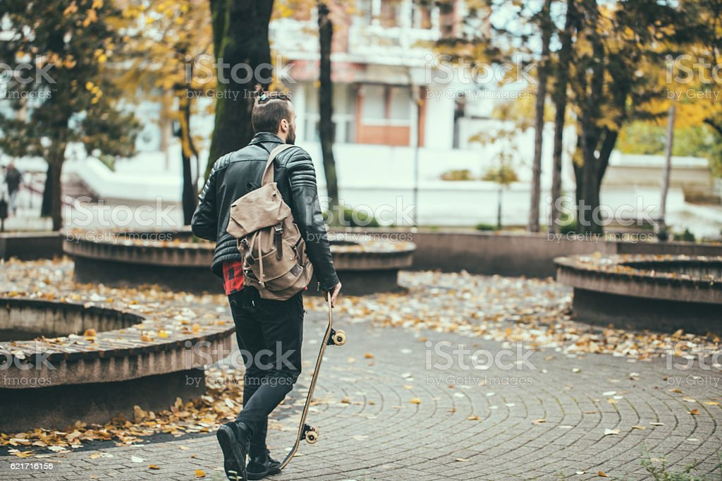 Hipster with skateboard stock photo
