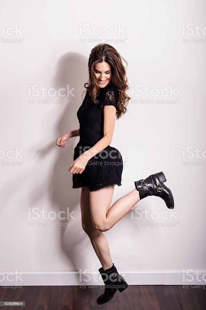 Hipster woman in dress and boots jumping out of joy stock photo