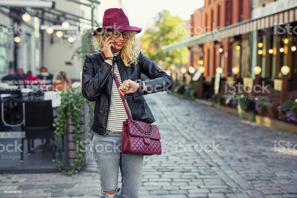 Hipster woman looking at her smartwatch and talking on cellphone stock photo