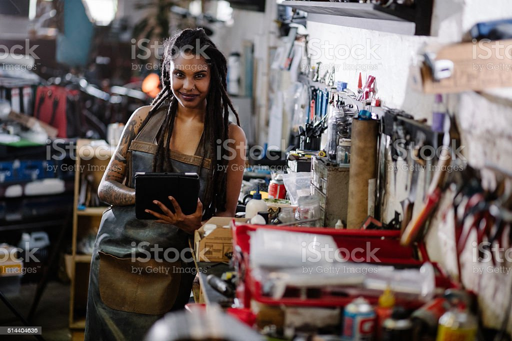Hipster woman with digital tablet surrounded by tools in worksho stock photo