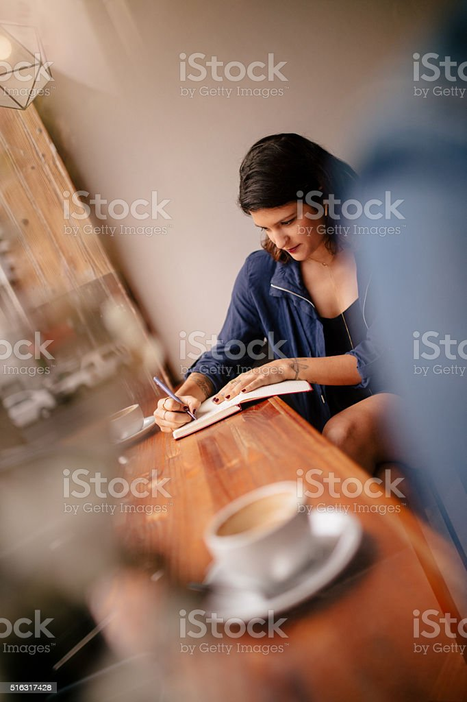Hipster Woman Writing at Window Seat in Coffee Shop stock photo