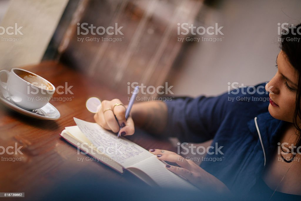 Hipster Woman Writing Journal at Window Seat in Coffee Shop stock photo