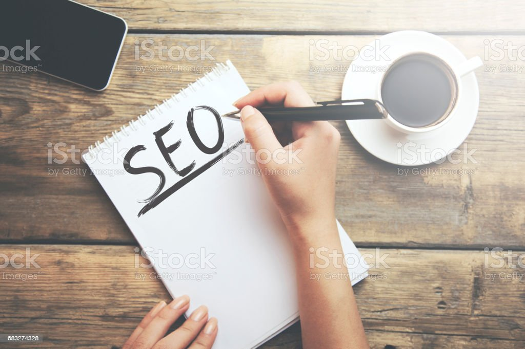 Hipster Writing SEO Concepts on his Note stock photo