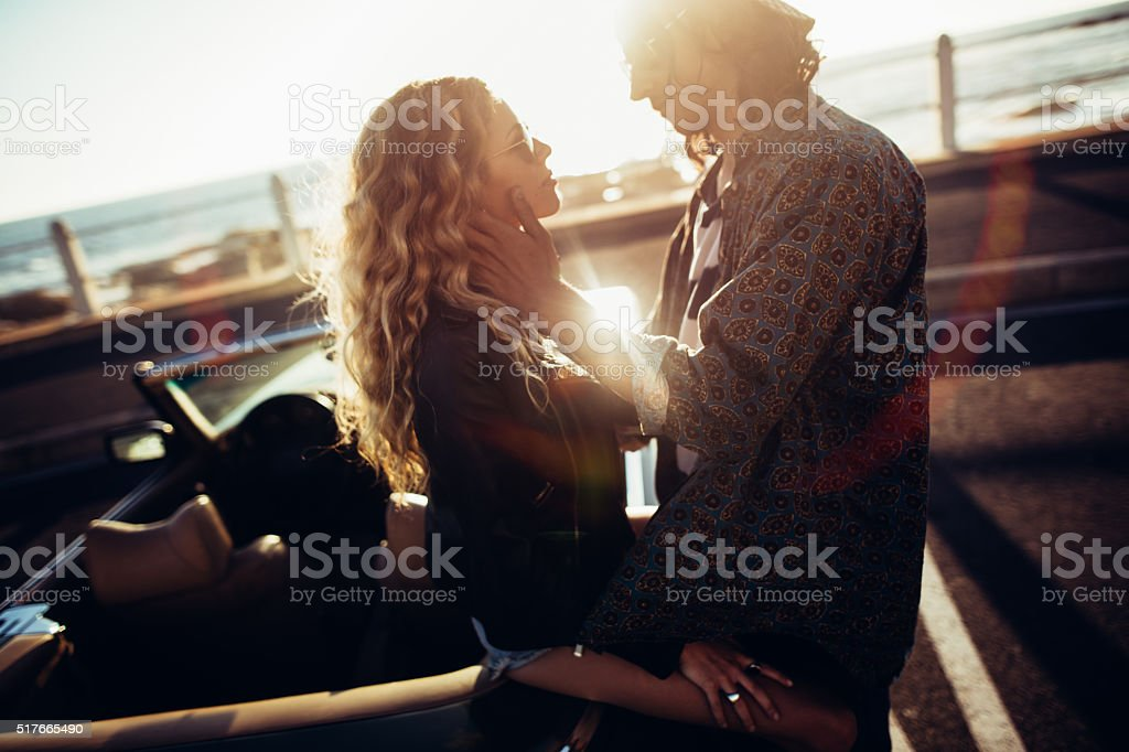 Hipster young men cuddling his girlfriend leaning to a vintage...