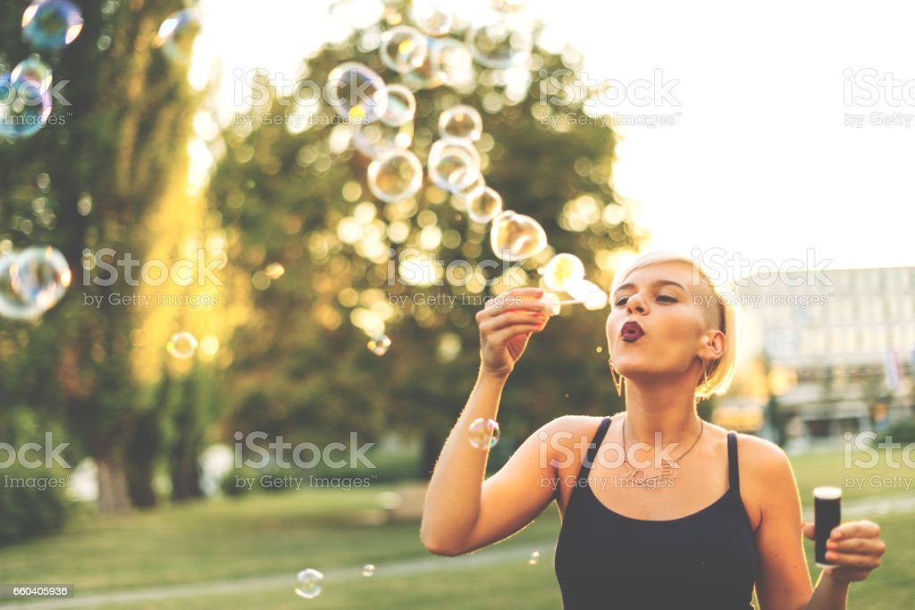 Hipster young woman in park on sunny summer day, blowing bubbles stock photo