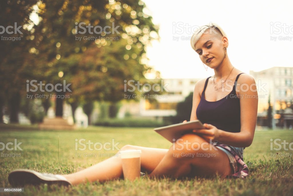 Hipster young woman in park on sunny summer day, relaxing and enjoying sun stock photo