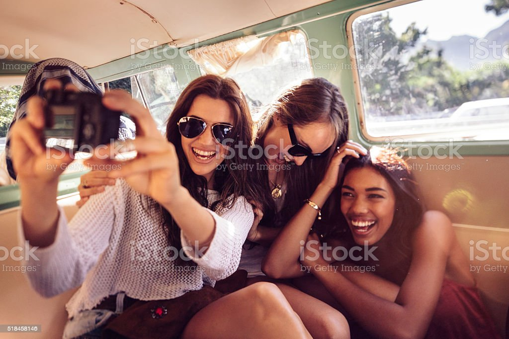 Hipster young women taking selfie inside a vintage van stock photo
