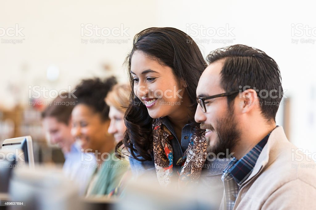 Hispanic adult college students studying together in computer lab stock photo