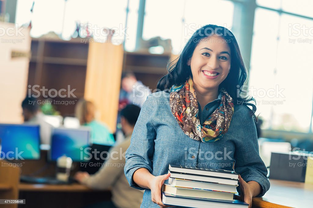 Hispanic adult student checking out books from college library stock photo