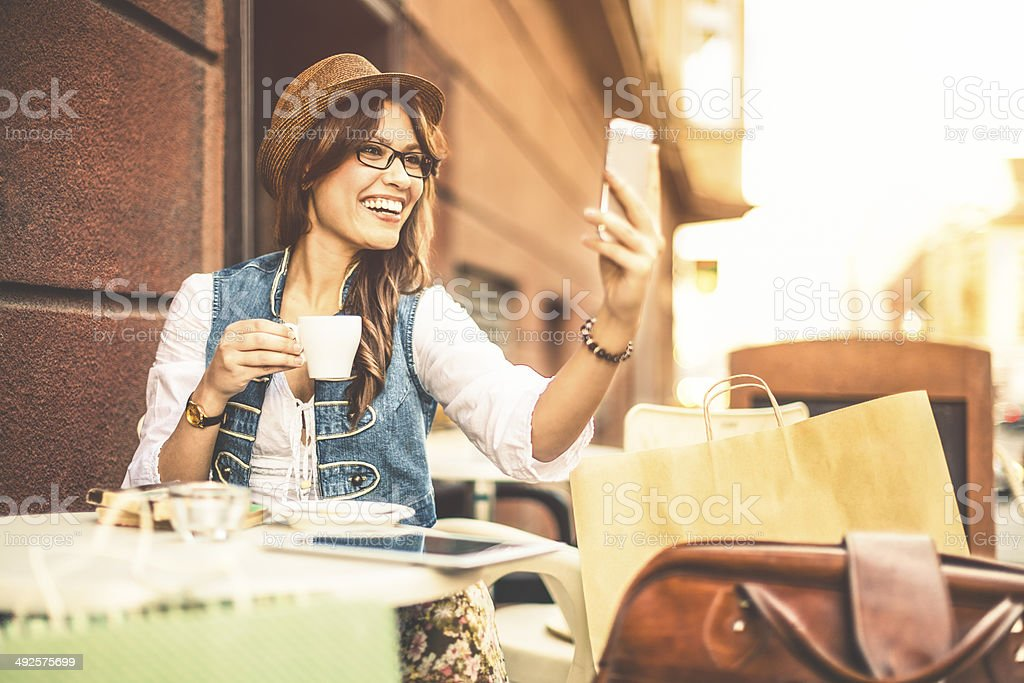 Hispanic beauty texting and enjoying a cup of coffee stock photo