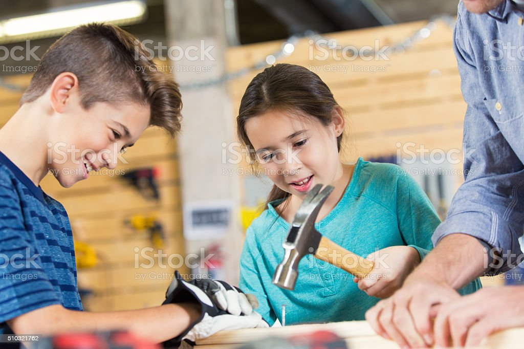 Hispanic boy and girl building something with father in workshop stock photo