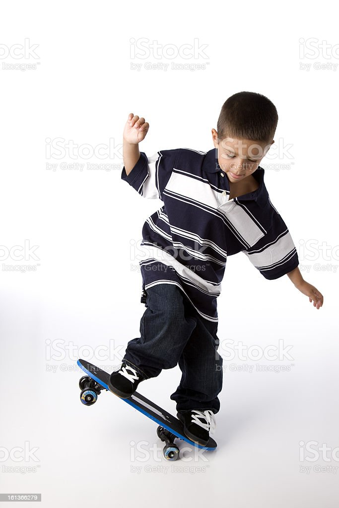 Hispanic Boy Does Tricks on Skateboard royalty-free stock photo