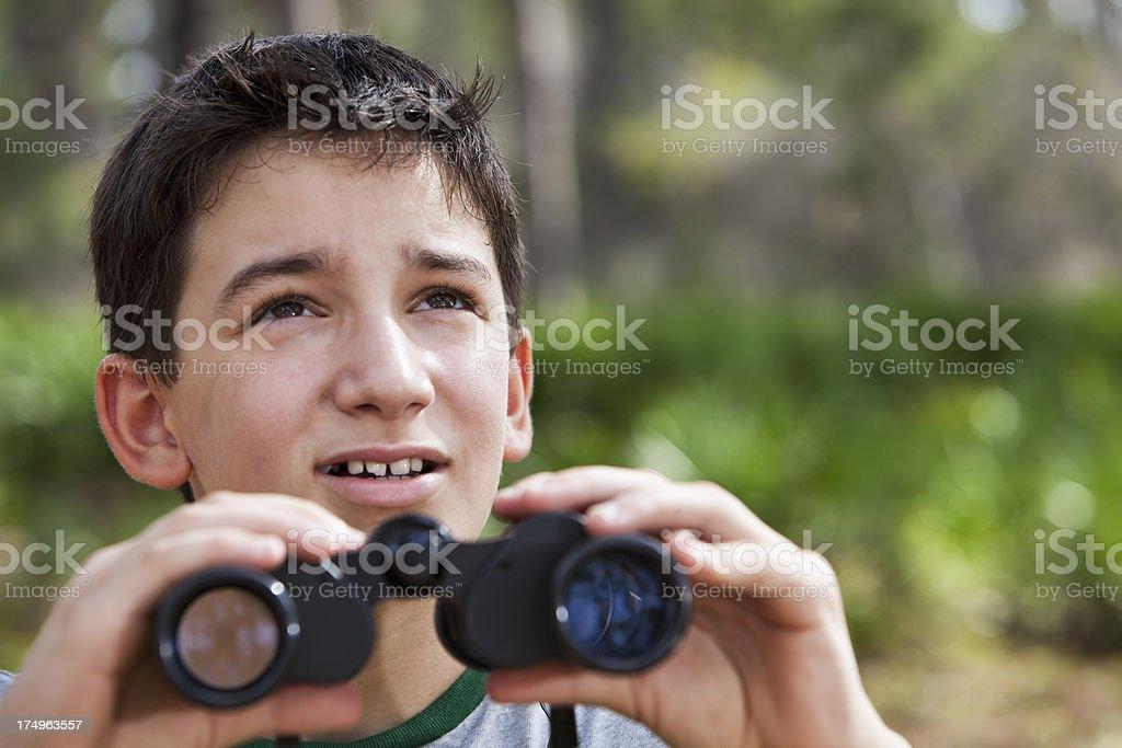 Hispanic boy in woods with binoculars stock photo