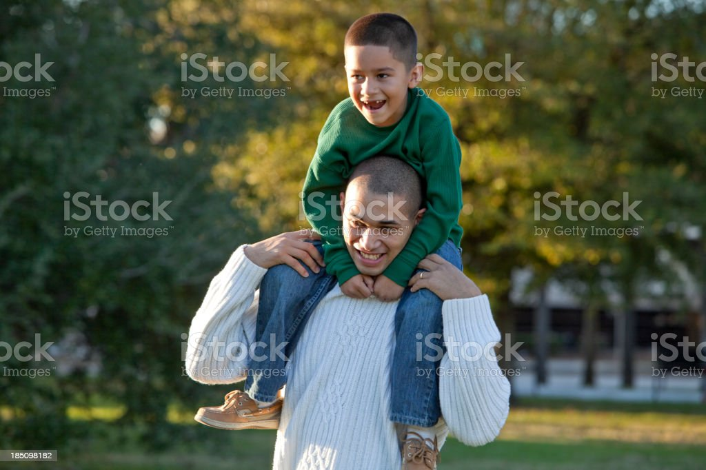 Hispanic boy riding on father's shoulders stock photo