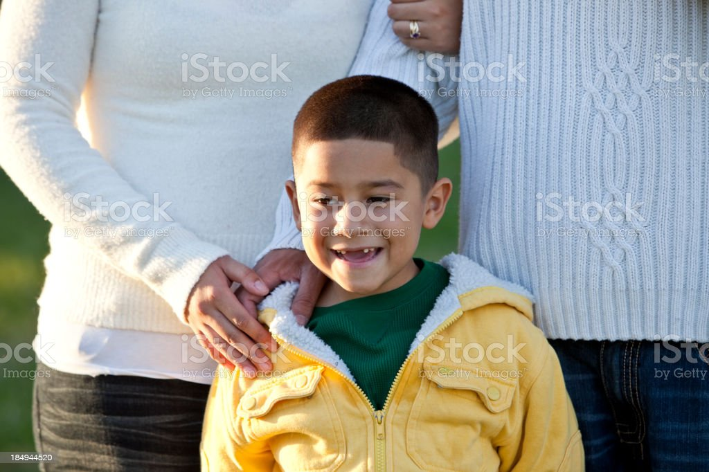 Hispanic boy standing with parents stock photo