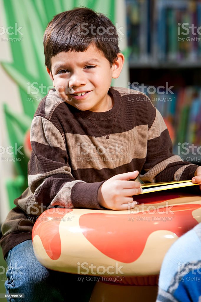 Hispanic boy with book in library stock photo