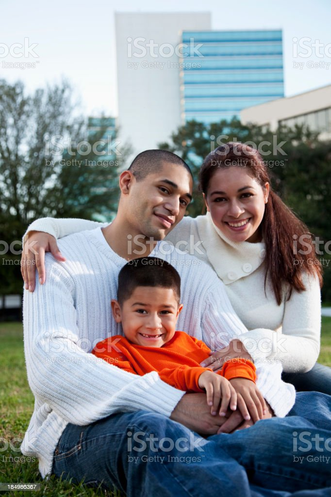 Hispanic boy with parents in city park stock photo