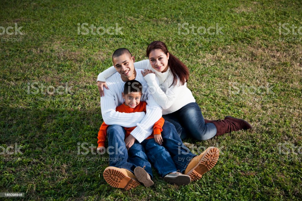 Hispanic boy with parents on grass stock photo