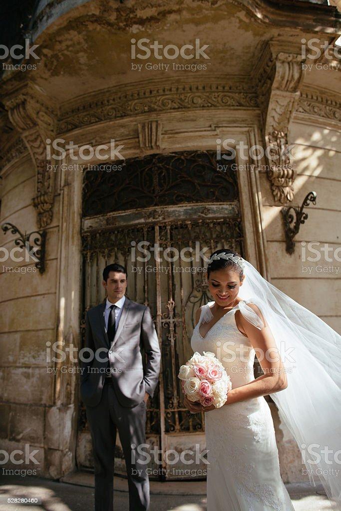 Hispanic bride and groom outside a home in Havana Cuba stock photo