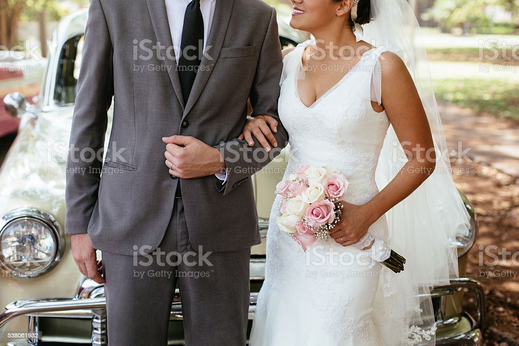 Hispanic bride holding groom's arm stock photo