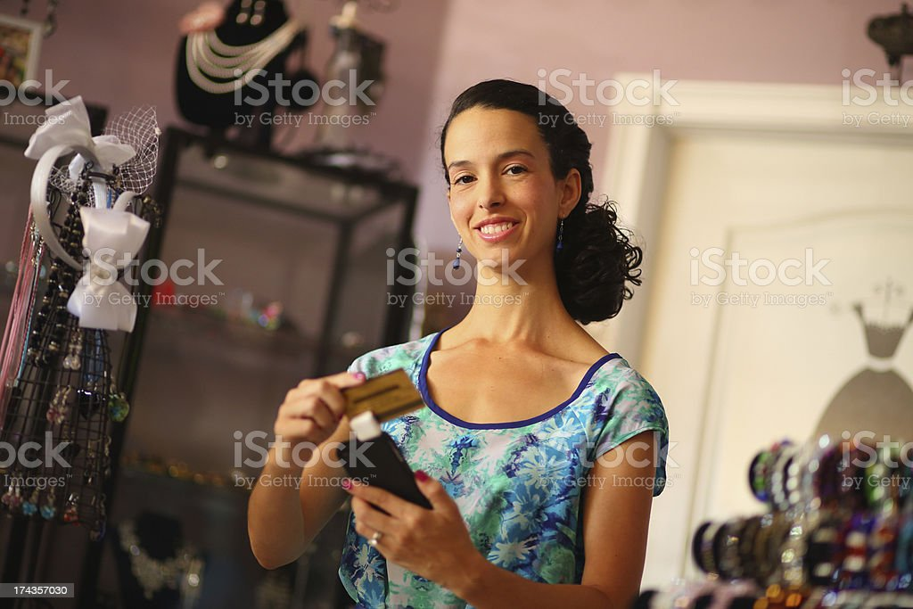 Hispanic Business Owner Swiping Credit Card with Smartphone stock photo