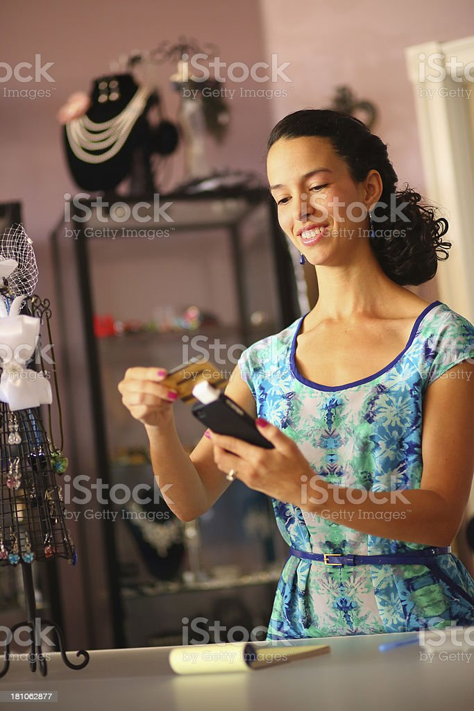 Hispanic Business Owner Swiping Credit Card with Smartphone royalty-free stock photo