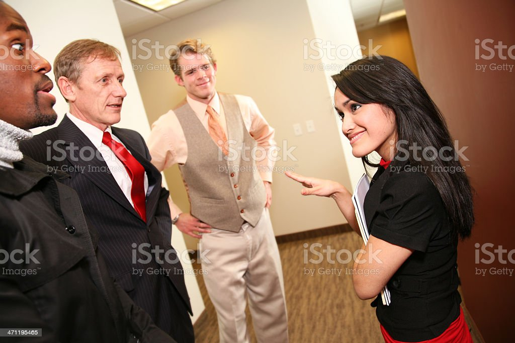 Hispanic Business Woman Explaining Something to Co-Workers royalty-free stock photo