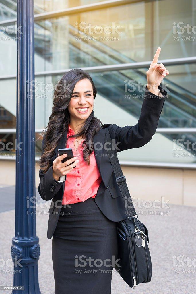 Hispanic Business Women Hailing An Uber stock photo