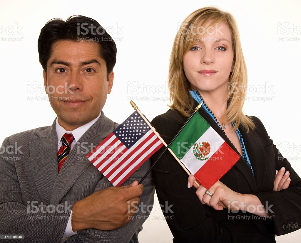 Hispanic businessman and Caucasian businesswoman hold Mexican & American flags royalty-free stock photo