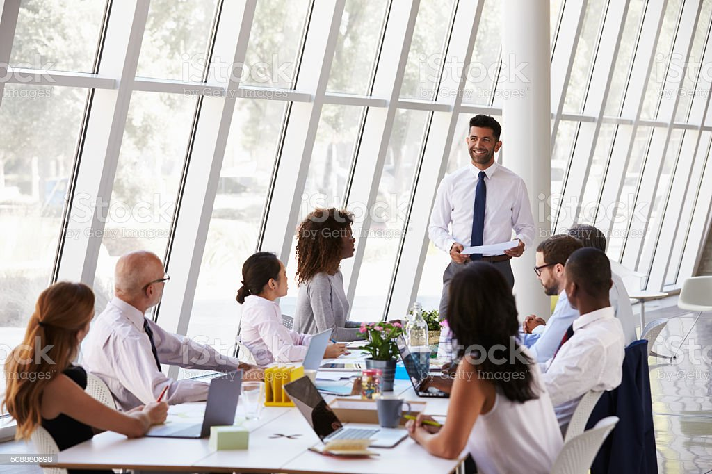 Hispanic Businessman Leading Meeting At Boardroom Table stock photo