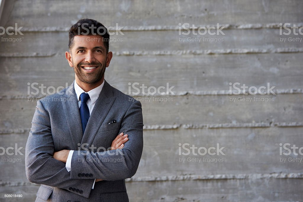 Hispanic Businessman Standing Against Wall In Modern Office stock photo