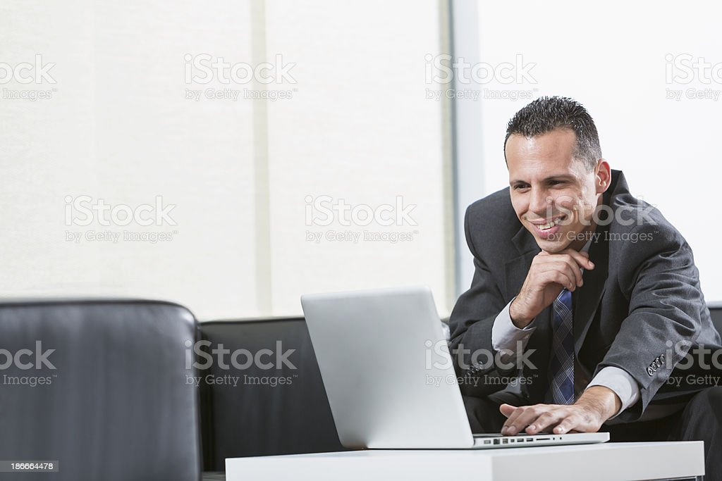Hispanic businessman wearing business suit using laptop computer royalty-free stock photo