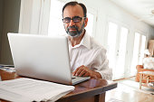 Hispanic Businessman Working From Home On Computer