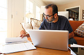 Hispanic Businessman Working From Home Talking On Cell Phone