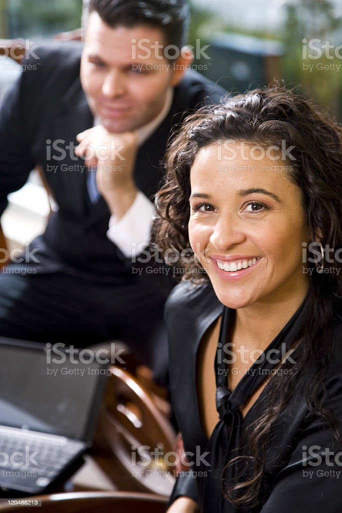Hispanic businesswoman and male coworker in office royalty-free stock photo
