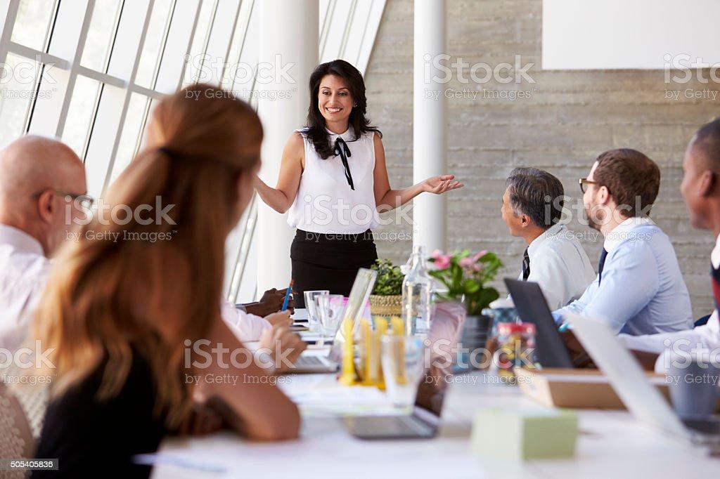 Hispanic Businesswoman Leading Meeting At Boardroom Table stock photo