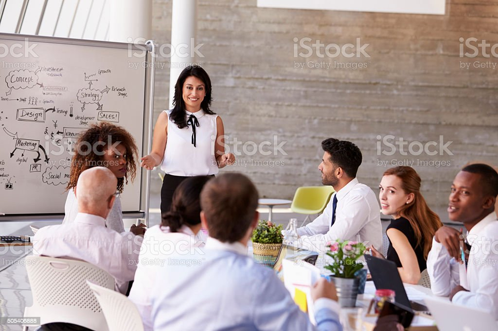 Hispanic Businesswoman Leading Meeting At Boardroom Table royalty-free stock photo