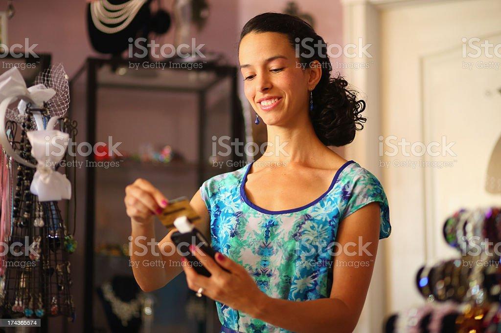 Hispanic businesswoman swiping credit card with smart phone stock photo