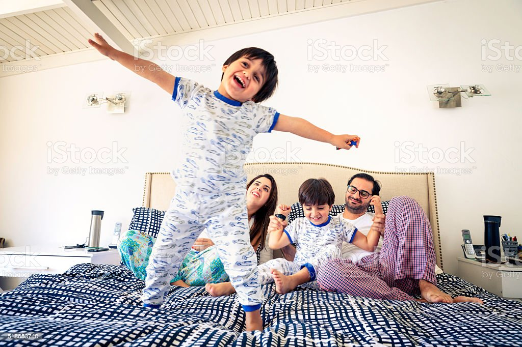 Hispanic children feet in bed close-up with parents stock photo