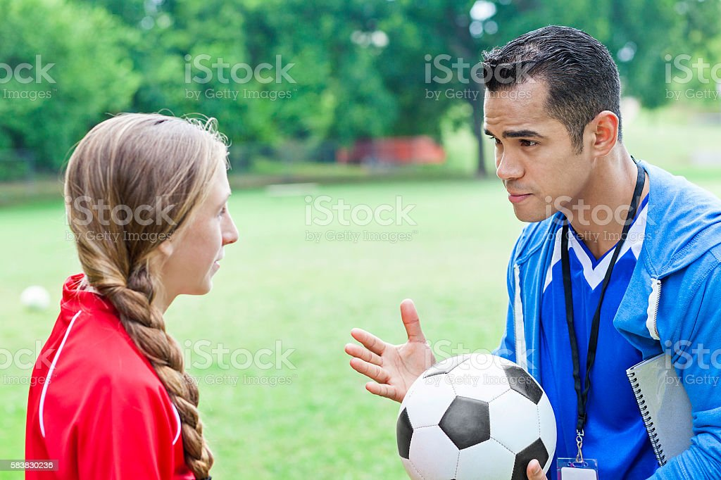 Hispanic coach talks with player during soccer game stock photo
