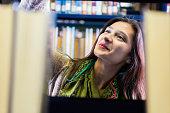Hispanic college girl searching bookshelves for library book